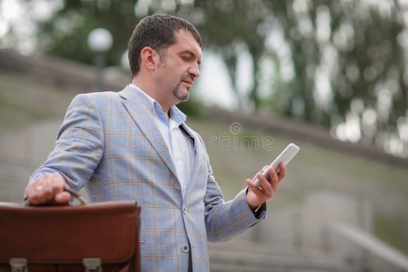Uomo di affari che manda un sms con un telefono Direttore con la cartella su un fondo vago Concetto di professionalità Copi lo sp fotografie stock libere da diritti