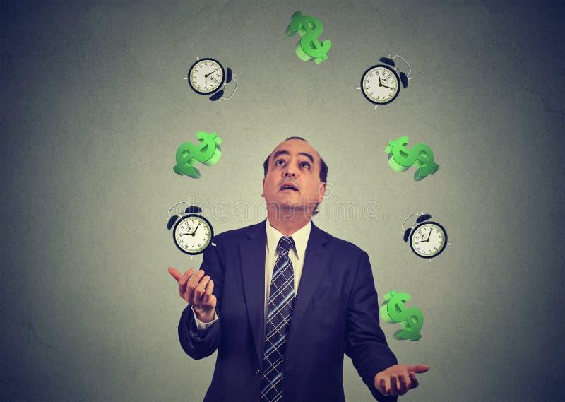 Uomo di affari che manipola gettando sui simboli di dollaro delle sveglie Il tempo è denaro concetto fotografie stock libere da diritti