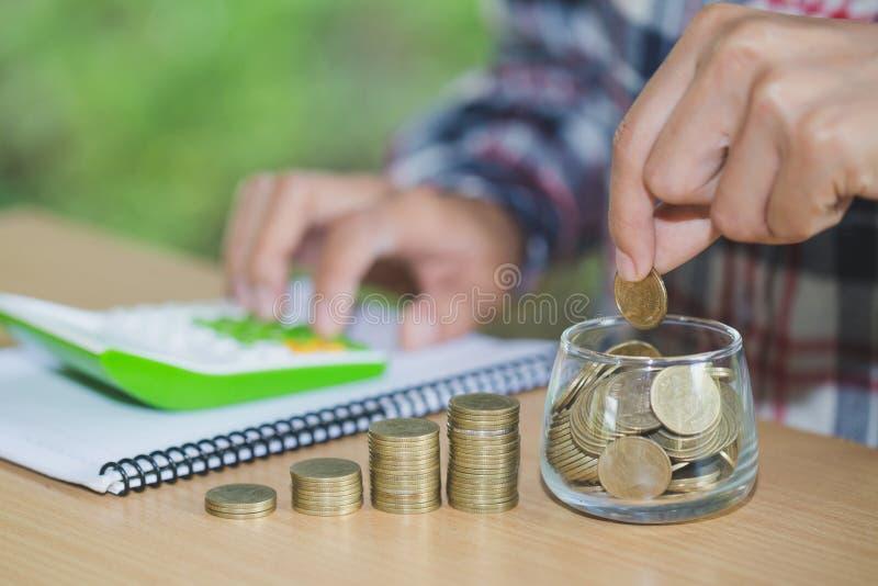Uomo di affari che mette moneta nella cassa di risparmio della bottiglia di vetro e rappresentare i suoi soldi tutti nella contab immagini stock libere da diritti