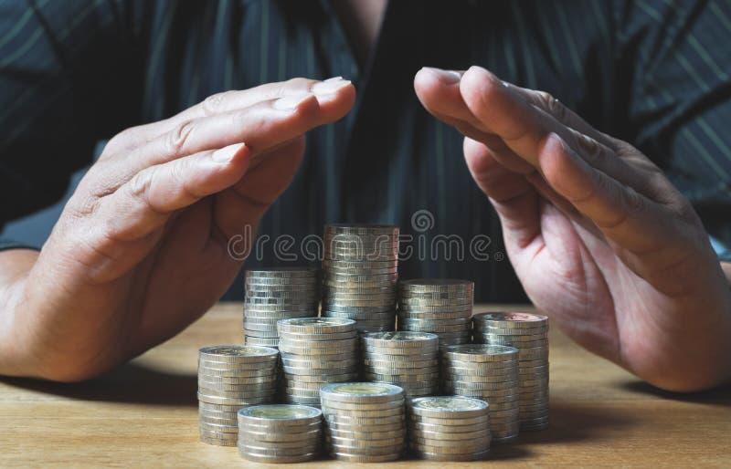 Uomo di affari che mette moneta sul mucchio della cassa di risparmio dei soldi e del accou immagini stock libere da diritti