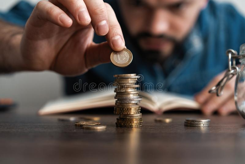 Uomo di affari che mette una moneta sulla cassa di risparmio della pila delle monete e rappresentare i suoi soldi tutti nel conce fotografie stock