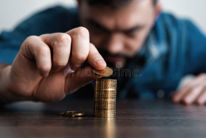 Uomo di affari che mette una moneta sulla cassa di risparmio della pila delle monete e rappresentare i suoi soldi tutti nel conce immagine stock