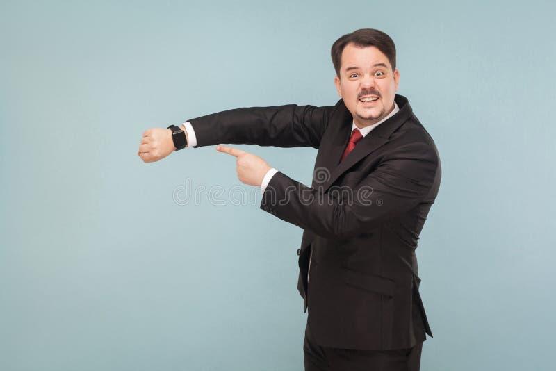 Uomo di affari che mostra all'orologio astuto immagini stock