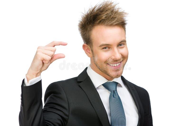 Uomo di affari che mostra piccola quantità di qualcosa immagini stock