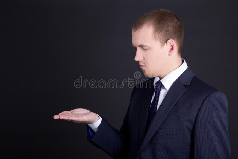Uomo di affari che mostra qualcosa sulla sua mano fotografia stock libera da diritti