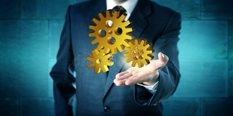 Uomo di affari che offre un azionamento dorato dell'ingranaggio 3D fotografie stock libere da diritti
