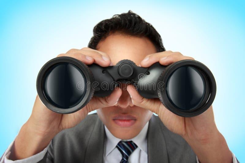 Uomo di affari che osserva con binoculare fotografie stock