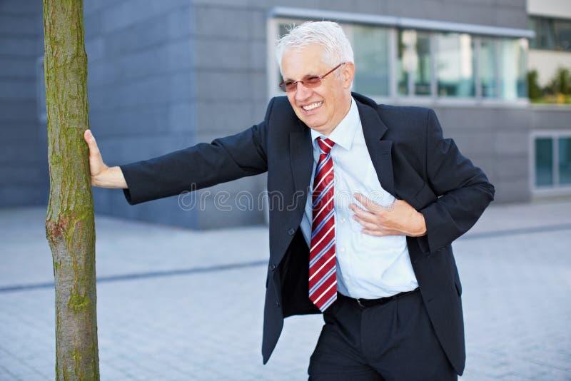 Uomo di affari che ottiene un attacco di cuore immagine stock