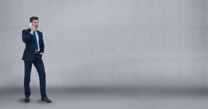 Uomo di affari che parla sul telefono contro il fondo grigio della parete immagine stock