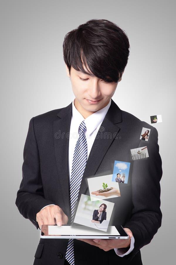 Uomo di affari che per mezzo del pc della compressa fotografie stock