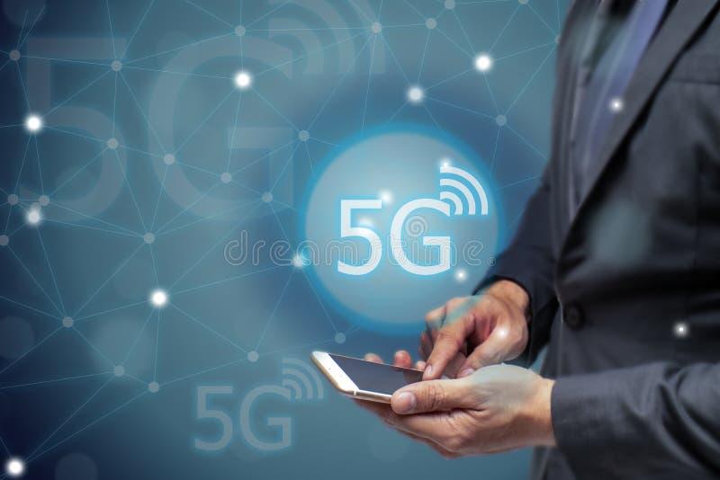 Uomo di affari che per mezzo del telefono cellulare con tecnologia wireless della rete 5g per collegare ogni comunicazione, Inter immagine stock