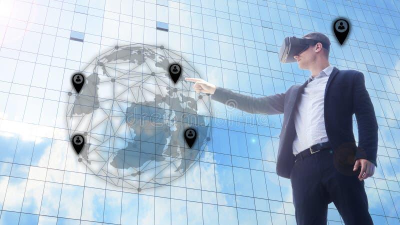 Uomo di affari che per mezzo della cuffia avricolare di VR ed interagendo con il mondo dell'oggetto fotografia stock