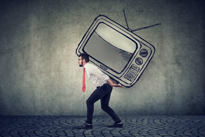 Uomo di affari che porta un grande set televisivo sul suo indietro immagine stock libera da diritti