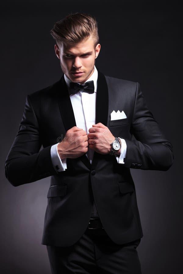 Uomo di affari che posa sul nero con le mani sul rivestimento fotografia stock