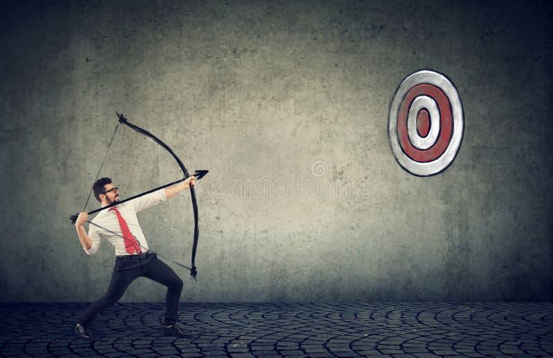 Uomo di affari che prova a colpire un obiettivo il suo scopo con l'arco e la freccia fotografia stock