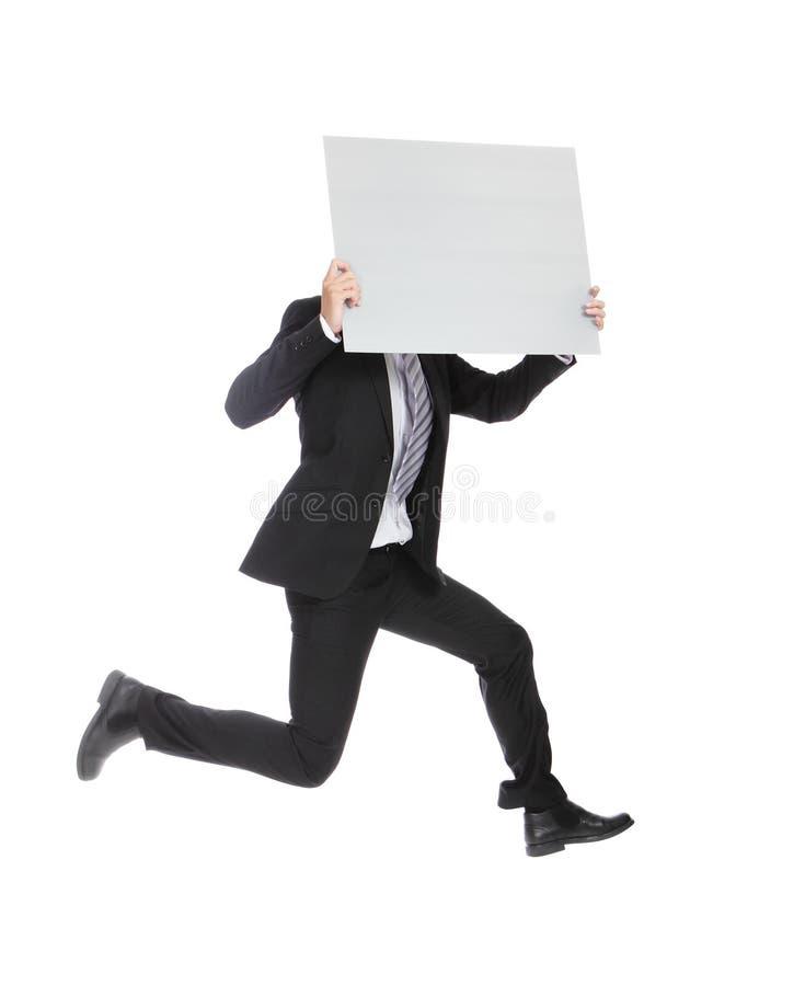 Uomo di affari che salta e che tiene tabellone per le affissioni fotografia stock
