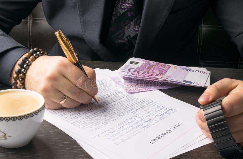 Uomo di affari che scrive un trattato o un contratto alla tavola e che lavora ai documenti nell'ufficio, concetto di affari fotografia stock