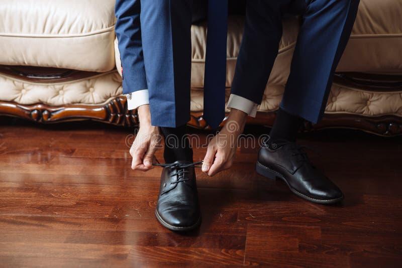 Uomo di affari che si agghinda con le scarpe classiche e eleganti Governi l'uso sul giorno delle nozze, legando i pizzi e la prep immagine stock libera da diritti