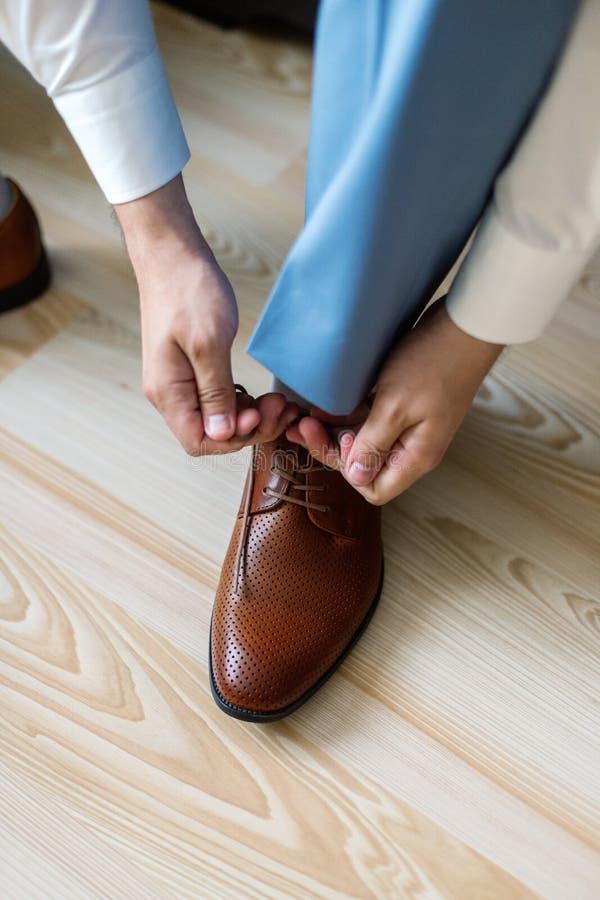 Uomo di affari che si agghinda con le scarpe classiche e eleganti Governi l'uso sul giorno delle nozze, legando i pizzi e la prep immagini stock libere da diritti