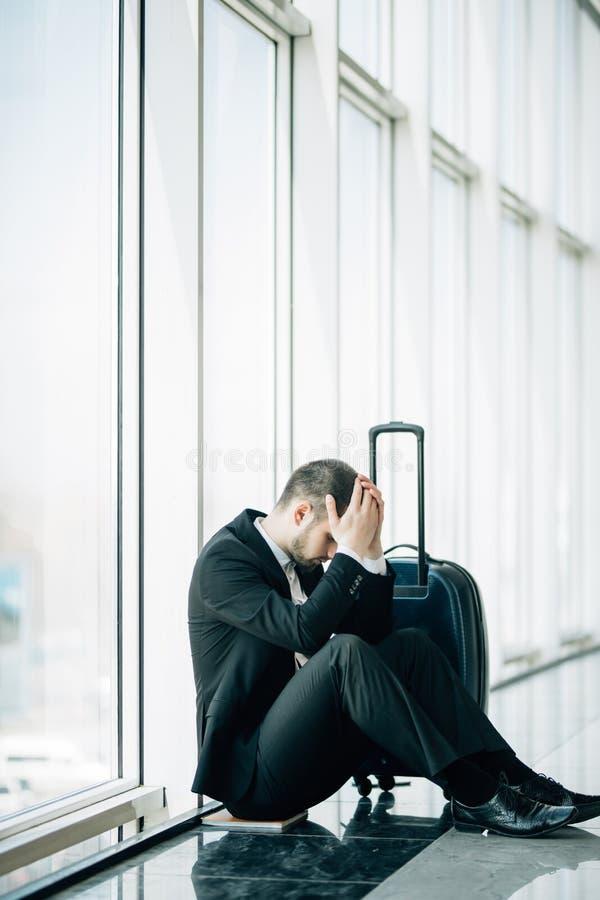 Uomo di affari che si siede all'aeroporto terminale sul pavimento con il ritardo di volo della valigia, un tocco di due mani alla fotografie stock libere da diritti