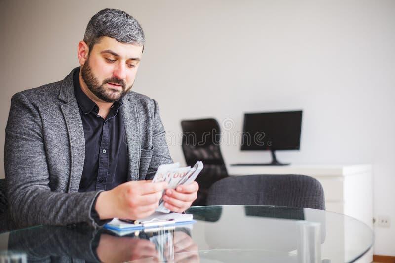 Uomo di affari che si siede allo scrittorio ed al contratto di firma L'uomo prende il dono per la firma del contratto Di alta ris fotografie stock
