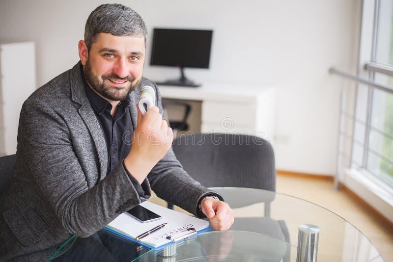 Uomo di affari che si siede allo scrittorio ed al contratto di firma L'uomo prende il dono per la firma del contratto Di alta ris immagini stock