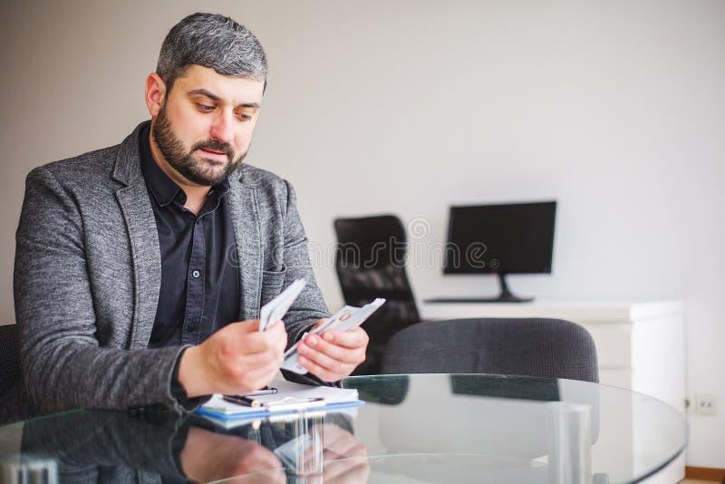 Uomo di affari che si siede allo scrittorio ed al contratto di firma L'uomo prende il dono per la firma del contratto Di alta ris fotografia stock libera da diritti
