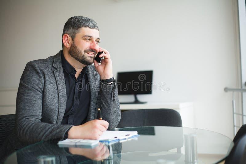 Uomo di affari che si siede allo scrittorio ed al contratto di firma L'uomo prende il dono per la firma del contratto Di alta ris fotografia stock