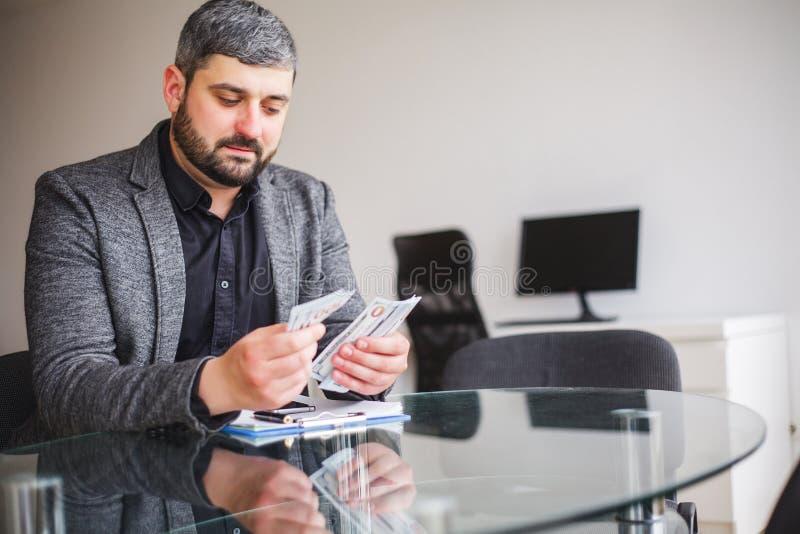 Uomo di affari che si siede allo scrittorio ed al contratto di firma Prese dell'uomo immagini stock libere da diritti