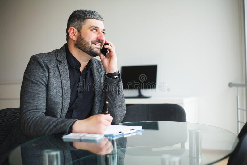 Uomo di affari che si siede allo scrittorio ed al contratto di firma Prese dell'uomo immagine stock libera da diritti