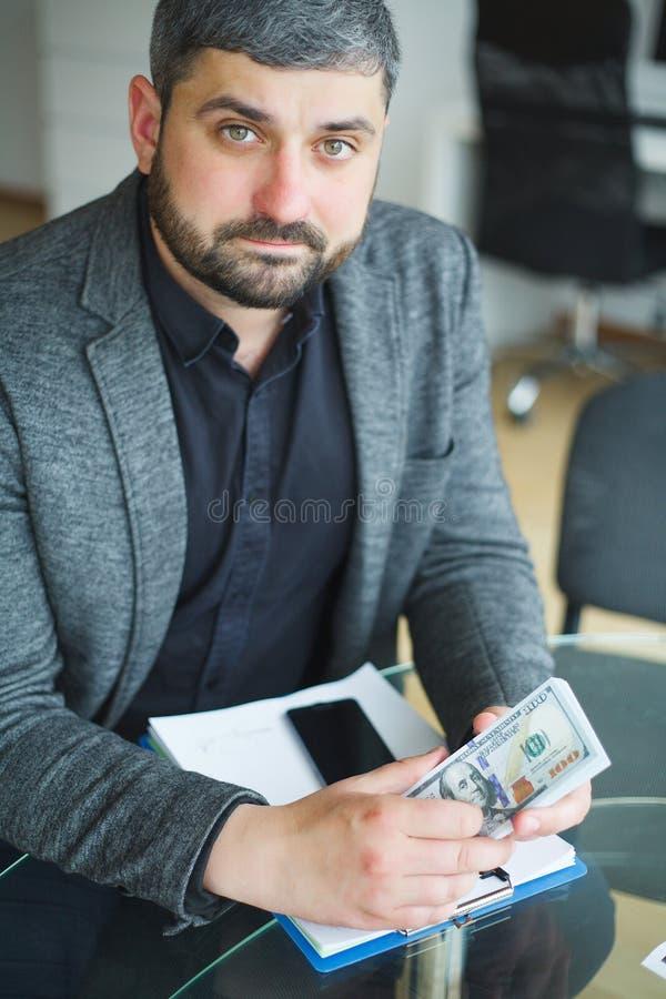 Uomo di affari che si siede allo scrittorio ed al contratto di firma Prese dell'uomo fotografia stock libera da diritti
