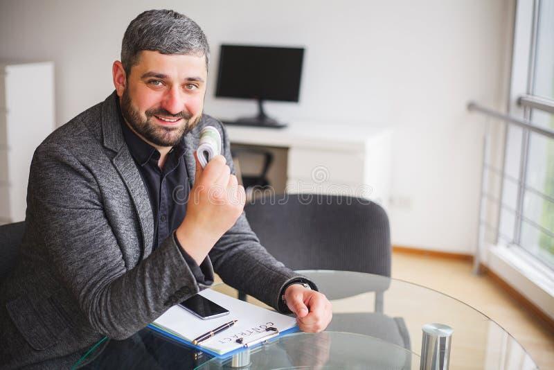 Uomo di affari che si siede allo scrittorio ed al contratto di firma Prese dell'uomo fotografie stock libere da diritti