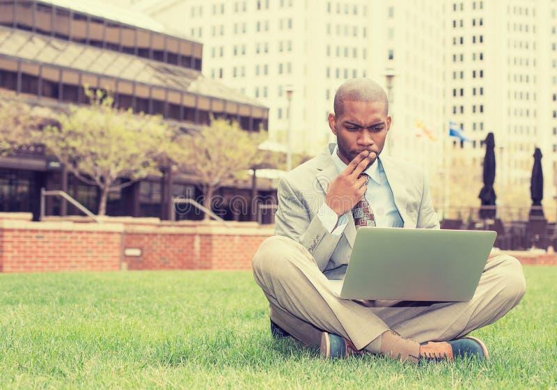 Uomo di affari che si siede fuori dell'ufficio corporativo che lavora al computer immagine stock libera da diritti