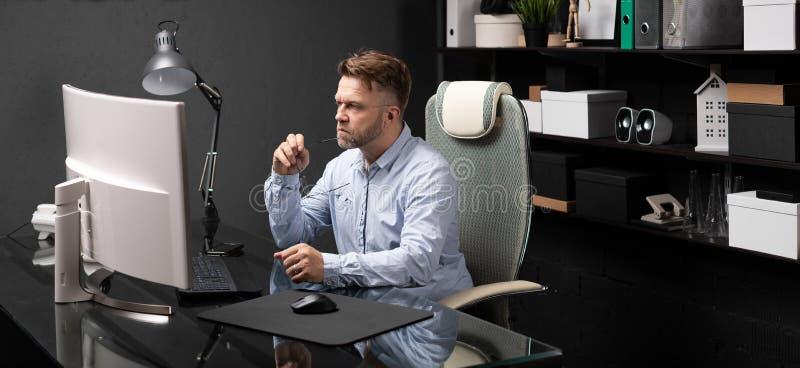 Uomo di affari che si siede nell'ufficio allo scrittorio del computer e che tiene il suo dispositivo d'ancoraggio della bocca dei fotografia stock