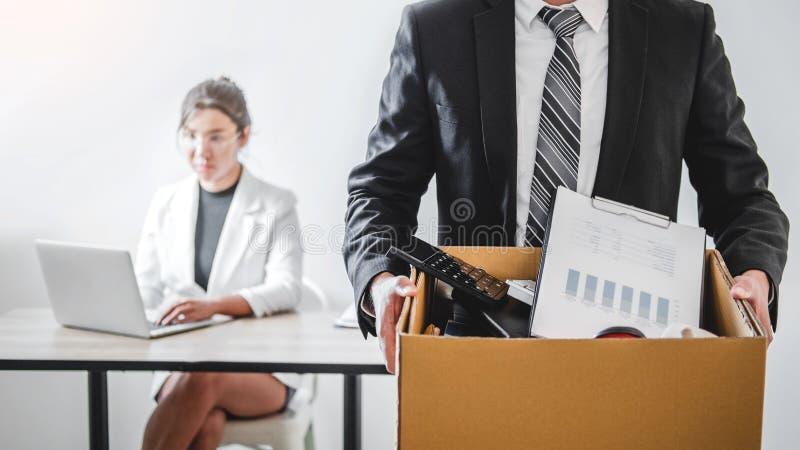 Uomo di affari che sollecita con la lettera di dimissioni per smesso un lavoro che imballa la scatola e che lascia l'ufficio, con fotografia stock