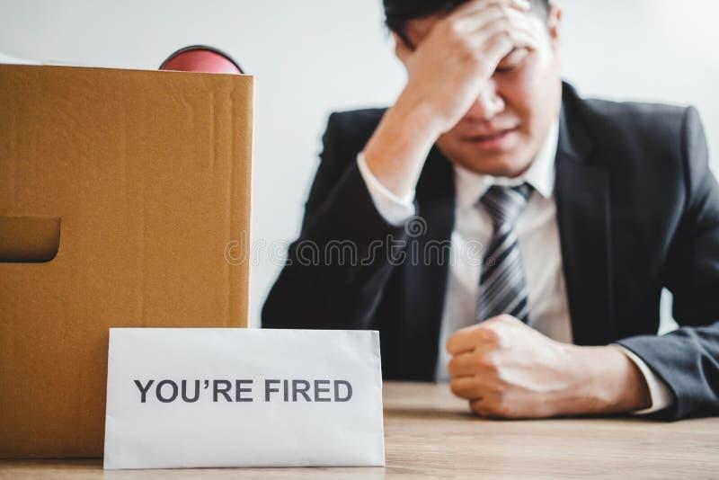 Uomo di affari che sollecita con la lettera di dimissioni per smesso un lavoro che imballa la scatola e che lascia l'ufficio, con fotografia stock libera da diritti