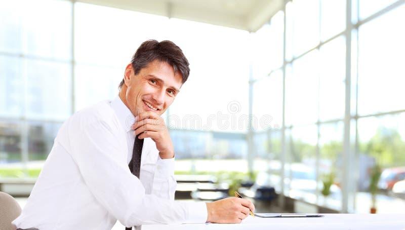 Uomo di affari che sorride all'ufficio immagine stock libera da diritti
