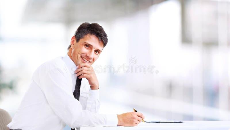 Uomo di affari che sorride all'ufficio immagine stock