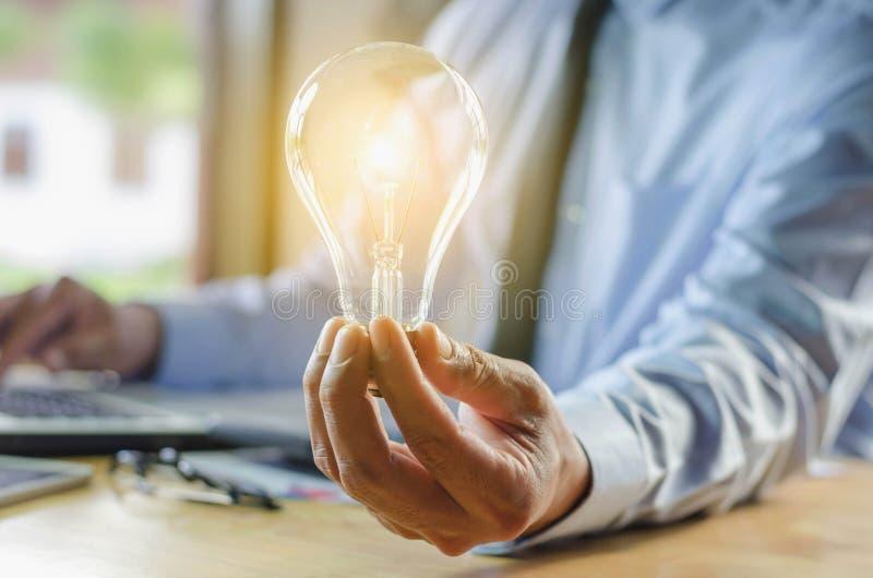 uomo di affari che tiene lampadina, idea di concetto con innovazione fotografia stock