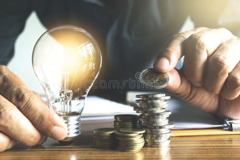 Uomo di affari che tiene lampadina sullo scrittorio in ufficio e in writin fotografie stock