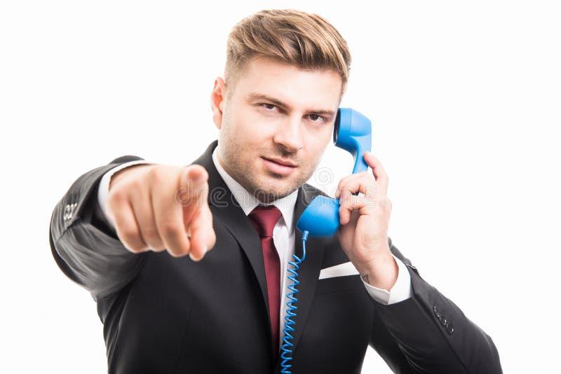 Uomo di affari che tiene ricevitore telefonico blu che indica macchina fotografica immagini stock libere da diritti