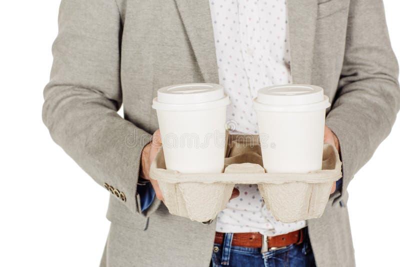 Uomo di affari che tiene un cassetto dell'introito fuori delle tazze di caffè a gettare fotografia stock
