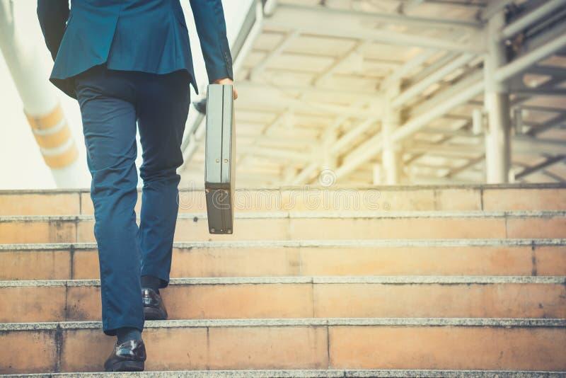 Uomo di affari che tiene una cartella che cammina sulle scale nel ro immagine stock libera da diritti