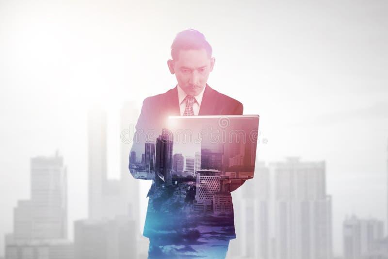 Uomo di affari con il computer della compressa della tenuta di esposizione multipla fotografia stock