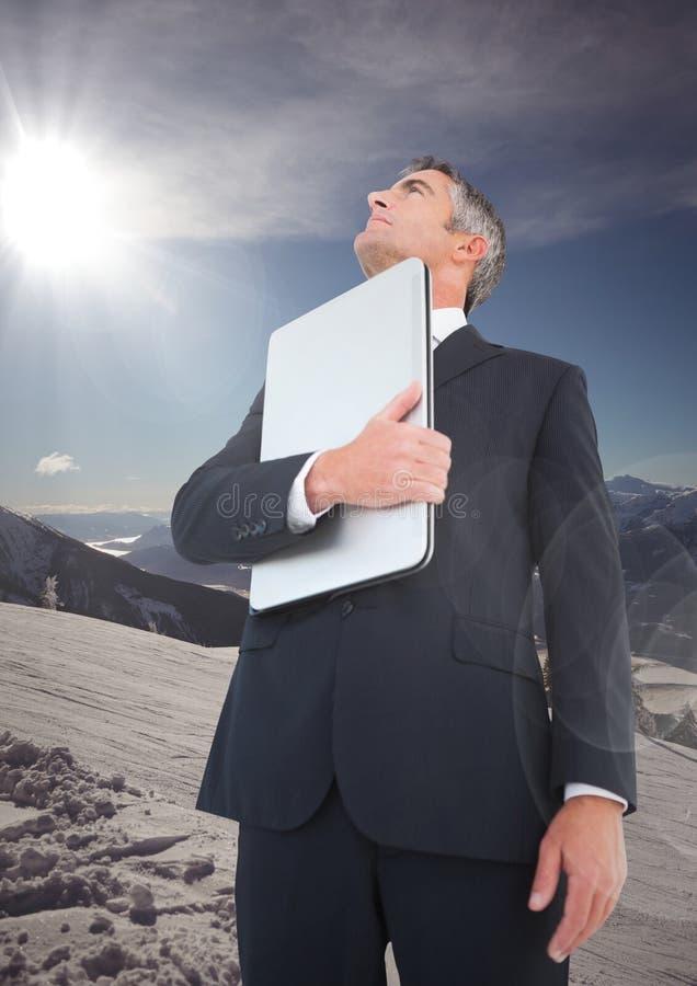 Uomo di affari con il computer portatile che cerca sulla montagna immagine stock