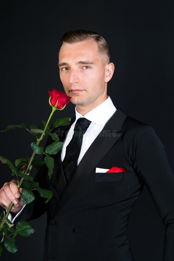Uomo di affari con il fiore della rosa rossa su fondo nero fotografie stock