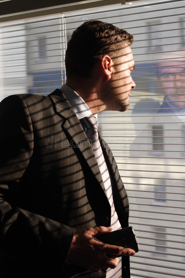 Uomo di affari con il telefono che osserva attraverso i ciechi di finestra immagine stock