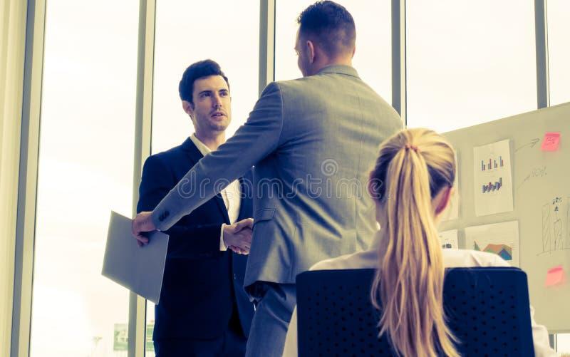 Uomo di affari con la stretta di mano con incoraggiare della donna e del partner fotografia stock