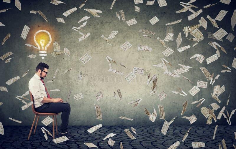 Uomo di affari con le idee luminose per mezzo di un computer portatile che costruisce i soldi online dei guadagni di affari immagini stock libere da diritti