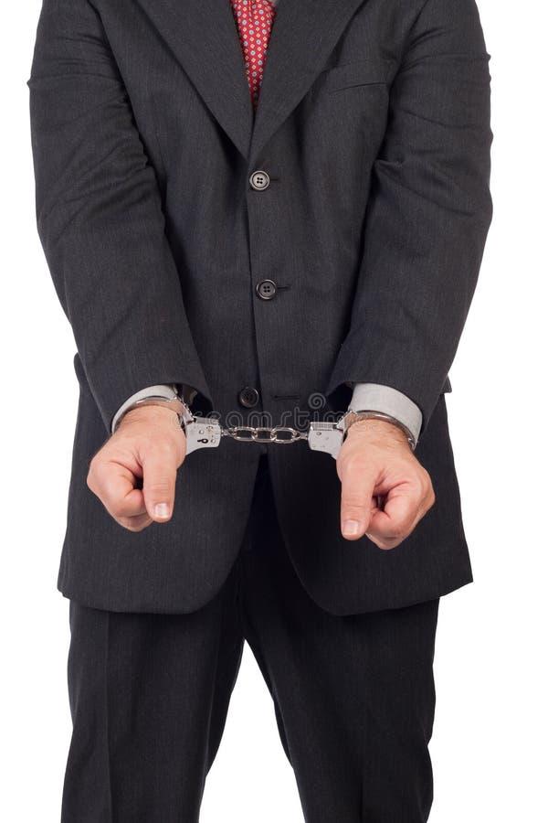 Uomo di affari con un vestito nero in manette immagine stock libera da diritti